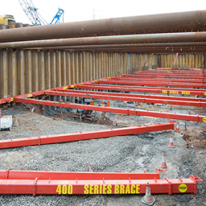 Multiple red MGF 400 Series Struts in an excavation on a project site