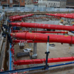 Installed red MGF hydraulic braces on a construction site