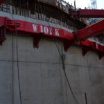 Up close view of red MGF hydraulic bracing systems at a major excavation