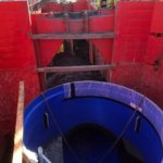 Inside look at a large blue pipe installed inside a red trench box in the ground