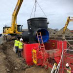 Large pipe being lowered into a red MGF trench box on a construction site